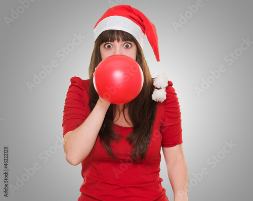 woman blowing balloon and wearing a christmas hat