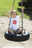 happy boy sitting on tyre swing
