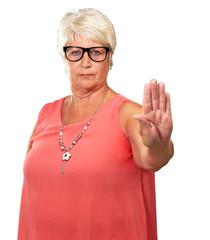 portrait of a senior woman showing stop sign