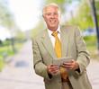Portrait Of A Senior Man Holding A Laptop