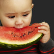 portrait of a handsome kid biting a watermelon over black backgr