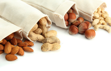 assortment of tasty nuts in bags, isolated on white