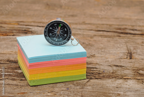 colorful post it note block with compass on wood table