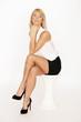 Blondes Model posiert auf Hocker