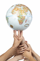 diverse group of hands lifting a globe