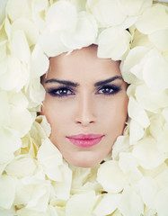 Beautiful woman face among rose petals
