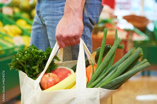 Leinwanddruck Bild Mann mit Beutel im Supermarkt