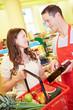 Verkäufer berät Kundin im Supermarkt