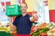 Mitarbeiter im Supermarkt hält Daumen hoch