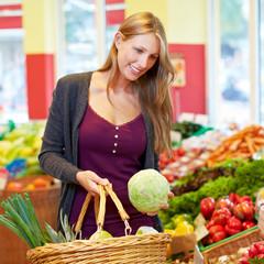 Frau kauft am Gemüsestand