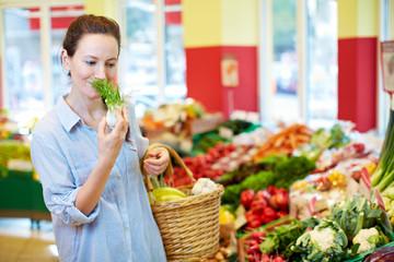 Frau riecht an Fenchel im Supermarkt