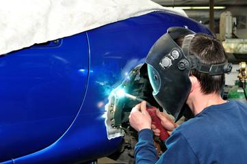 Worker welding car body.