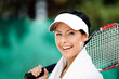 Tennis player with towel on her shoulders. Active pastime