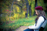 teen girl alone with cell phone  in autumn setting poster