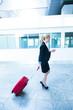 Geschäftsfrau mit Handy am Flughafen
