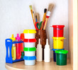 Tools of the artist: paints, brushes on a shelf in the children'