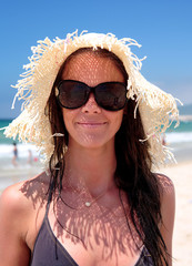 Sexy young female on beach with hat