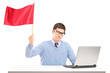 Sad man sitting with laptop and waving a red flag