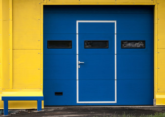 Texture of modern yellow garage wall with closed blue gate