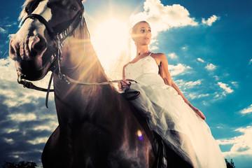 Braut mit Brautkleid reitet ein Pferd im Gegenlicht