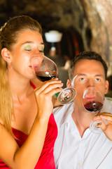 Mann und Frau probieren Wein im Keller