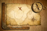 aged treasure map, ruler and old brass compass on wooden table t