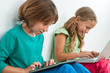 Two kids playing on tablet and laptop.