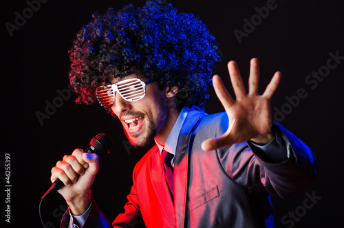 Young singer in afro wig singing at disco