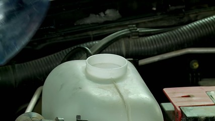 Pouring the windshield washer fluid into the tank