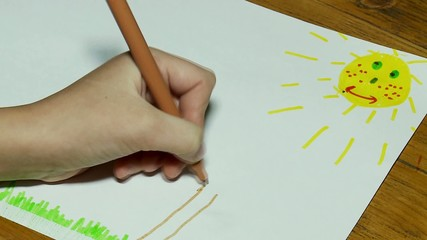 Child's hand draws a summer landscape (time lapse).