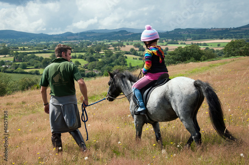Leading pony & young girl in countryside