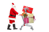 Santa Claus standing next to a shopping cart full of gifts
