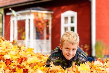 Blonder Junge im Herbstlaub vor Schwedenhaus liegend