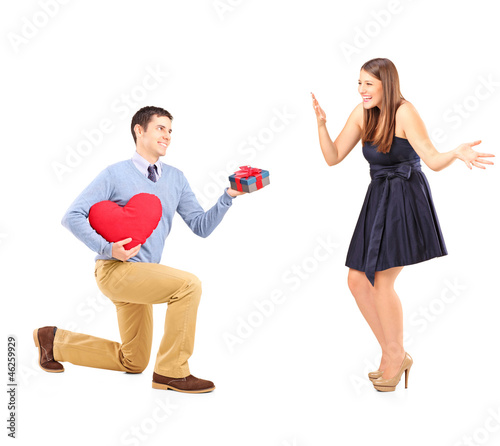 Smiling male giving flowers and excited female
