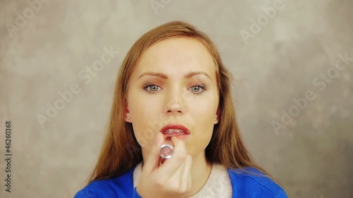 Young woman painting her lips by red lipstick