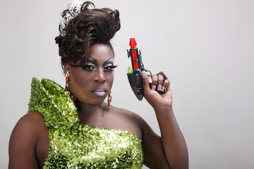 Drag queen wearing a green gown holding a scifi raygun.
