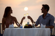 Romantic moments - Couple at beach sunset enjoying dinner