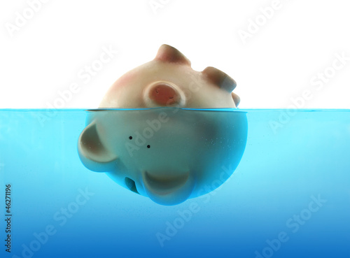 Piggy bank sinking in blue water