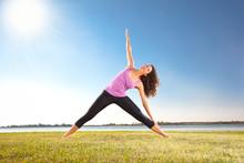 Schöne junge Frau macht Yoga-Übung auf grünem Gras
