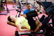 Woman doing leg exercise under personal trainer's supervision. A