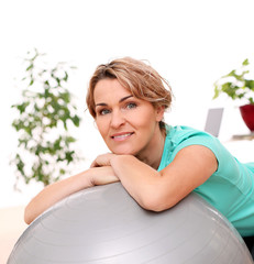 Cute and smiling middle aged woman with abs ball