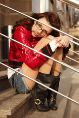 Beautiful redheaded girl sits on a stairs