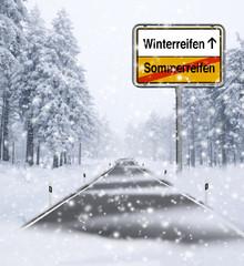 Schneefahrbahn mit Ortsschild Winterreifen