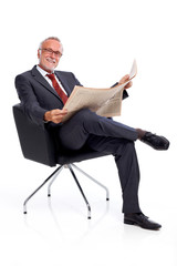 Sitting mature business man with newspaper