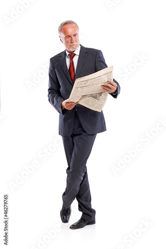 Mature business man reading newspaper, focused
