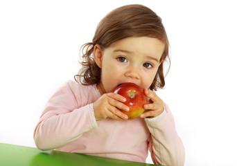 Ein Mädchen beißt in einen roten Apfel