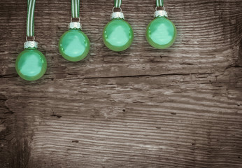 Vier grüne Kugeln vor Holz