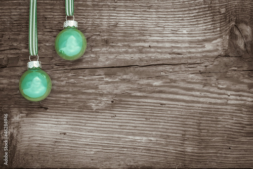 Zwei grüne Kugeln vor Holz