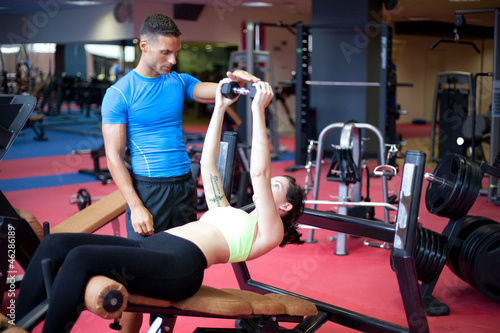 Young woman doing sit ups with the help of a personal trainer. S