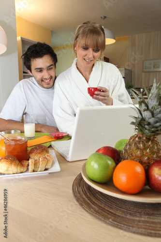 Young people having breakfast looking at computer